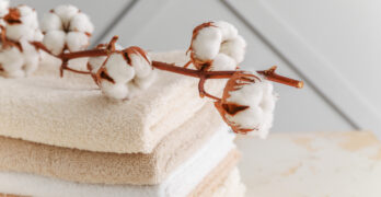 Soft clean towels with cotton flowers on table